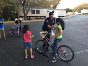 Officer smiling while talking to children on bicycles